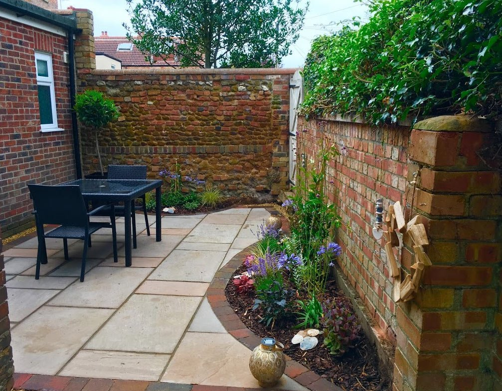 A small unused courtyard transformed with a new patio, brick borders and simple planting