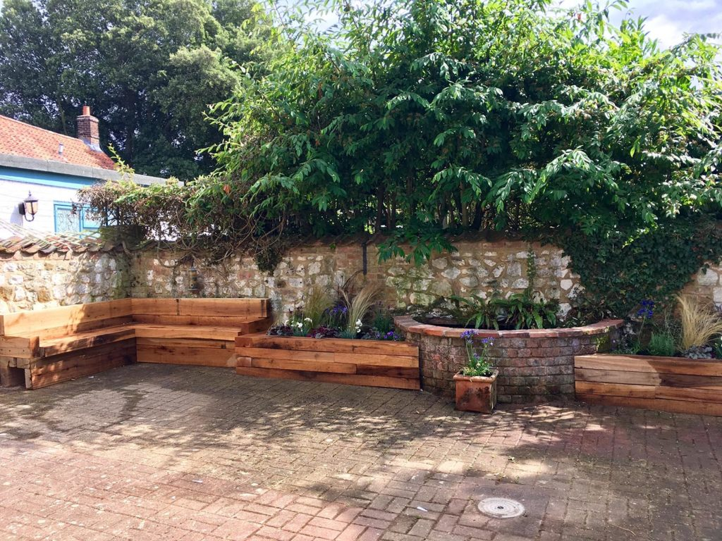 A small courtyard transformed with simple landscaping including oak sleeper seating, raised beds and a water feature from reclaimed bricks