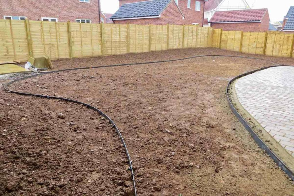 A very blank canvas - garden design with new patio, central lawn (turfed), steel edging and over 100 plants ready to go in