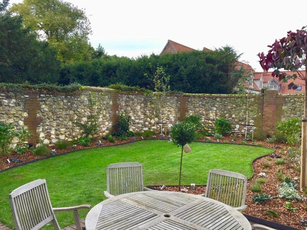 Small Garden Makeover in Thornham with over-seeded lawn, steel lawn edging, bark mulch and various trees
